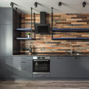 Пример оригинального дизайна: линейная кухня в стиле лофт с серыми фасадами, коричневым фартуком, накладной раковиной и плоскими фасадами