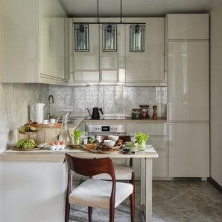 На фото: угловая кухня в современном стиле с плоскими фасадами, бежевыми фасадами, техникой из нержавеющей стали, серым полом и бежевой столешницей без острова с