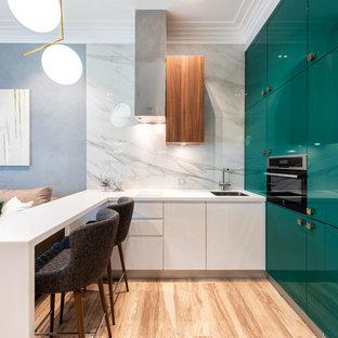 Идея дизайна: угловая кухня-гостиная в современном стиле с одинарной раковиной, плоскими фасадами, столешницей из акрилового камня, белым фартуком, белой столешницей, бирюзовыми фасадами, фартуком из каменной плиты, черной техникой, светлым паркетным полом, полуостровом и бежевым полом