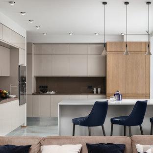 Неиссякаемый источник вдохновения для домашнего уюта: кухня-гостиная в современном стиле с плоскими фасадами, коричневым фартуком, полуостровом, бежевыми фасадами, белым полом и коричневой столешницей