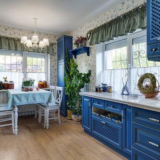 他の地域の広いおしゃれなキッチン (アンダーカウンターシンク、レイズドパネル扉のキャビネット、青いキャビネット、タイルカウンター、白いキッチンパネル、セラミックタイルのキッチンパネル、白い調理設備、無垢フローリング、アイランドなし) の写真