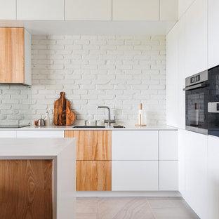 Пример оригинального дизайна интерьера: угловая кухня - столовая в современном стиле с врезной раковиной, плоскими фасадами, белыми фасадами, белым фартуком, фартуком из кирпича, техникой из нержавеющей стали, островом, бежевым полом и белой столешницей