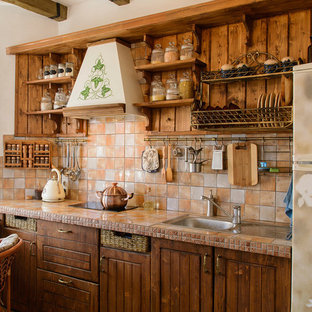Mid-sized mediterranean eat-in kitchen pictures - Mid-sized tuscan single-wall porcelain floor and red floor eat-in kitchen photo in Other with a drop-in sink, recessed-panel cabinets, tile countertops, multicolored backsplash, ceramic backsplash, paneled appliances and multicolored countertops