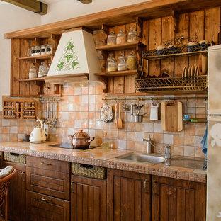 他の地域の中サイズの地中海スタイルのおしゃれなキッチン (ドロップインシンク、落し込みパネル扉のキャビネット、タイルカウンター、マルチカラーのキッチンパネル、セラミックタイルのキッチンパネル、パネルと同色の調理設備、磁器タイルの床、赤い床、マルチカラーのキッチンカウンター) の写真