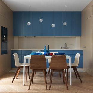 На фото: маленькая п-образная кухня в современном стиле с плоскими фасадами, синими фасадами, бежевым фартуком, черной техникой, бежевой столешницей, обеденным столом, светлым паркетным полом и бежевым полом без острова