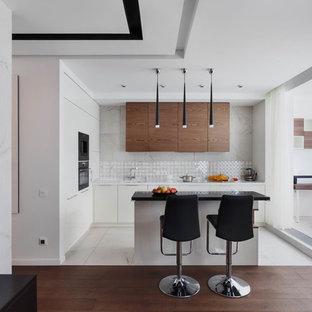 На фото: угловая кухня-гостиная среднего размера в современном стиле с врезной раковиной, плоскими фасадами, белыми фасадами, столешницей из акрилового камня, белым фартуком, фартуком из керамогранитной плитки, островом, белой столешницей, белым полом и черной техникой