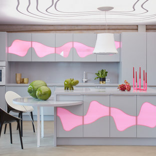 Пример оригинального дизайна: параллельная кухня-гостиная в современном стиле с накладной раковиной, стеклянными фасадами, серыми фасадами, столешницей из акрилового камня, серым фартуком, белой техникой, островом, серой столешницей и бежевым полом