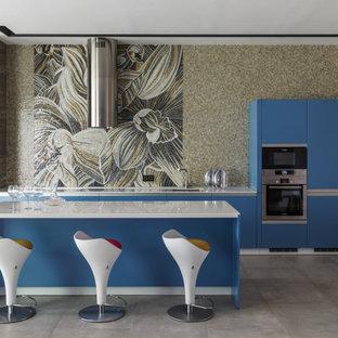 На фото: параллельная кухня в современном стиле с врезной раковиной, плоскими фасадами, синими фасадами, разноцветным фартуком, фартуком из плитки мозаики, техникой из нержавеющей стали, островом, серым полом и белой столешницей
