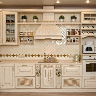 This is an example of a small asian l-shaped separate kitchen in Yekaterinburg with an undermount sink, raised-panel cabinets, beige cabinets, solid surface benchtops, beige splashback, mosaic tile splashback, white appliances, ceramic floors, no island, brown floor and beige benchtop.