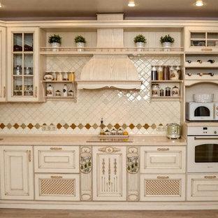 エカテリンブルクの小さいアジアンスタイルのおしゃれなキッチン (アンダーカウンターシンク、レイズドパネル扉のキャビネット、ベージュのキャビネット、人工大理石カウンター、ベージュキッチンパネル、モザイクタイルのキッチンパネル、白い調理設備、セラミックタイルの床、アイランドなし、茶色い床、ベージュのキッチンカウンター) の写真