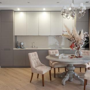 Пример оригинального дизайна интерьера: линейная кухня в стиле современная классика с обеденным столом, плоскими фасадами, серыми фасадами, фартуком из стекла, светлым паркетным полом, бежевым полом и белой столешницей без острова