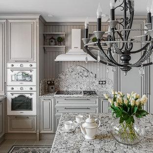 На фото: угловая кухня-гостиная среднего размера в классическом стиле с фасадами с выступающей филенкой, серыми фасадами, мраморной столешницей, фартуком из мрамора, полом из керамической плитки, островом, серым полом, серой столешницей, серым фартуком и белой техникой