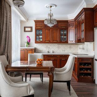 Неиссякаемый источник вдохновения для домашнего уюта: большая п-образная кухня в классическом стиле с столешницей из акрилового камня, бежевым фартуком, фартуком из керамической плитки, коричневым полом, белой столешницей, обеденным столом, фасадами с утопленной филенкой, темным паркетным полом и темными деревянными фасадами без острова