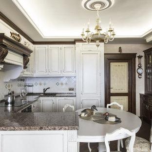 Пример оригинального дизайна: п-образная кухня в классическом стиле с накладной раковиной, белыми фасадами, полуостровом, коричневым полом, коричневой столешницей, фасадами с выступающей филенкой, разноцветным фартуком, фартуком из керамической плитки и техникой под мебельный фасад