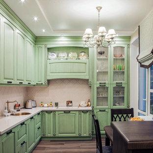 Пример оригинального дизайна интерьера: угловая кухня в стиле шебби-шик с обеденным столом, накладной раковиной, фасадами с выступающей филенкой, зелеными фасадами, бежевым фартуком, паркетным полом среднего тона, коричневым полом и белой столешницей
