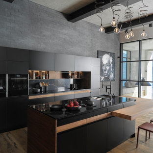 Design ideas for a mid-sized contemporary galley kitchen in Saint Petersburg with black appliances, with island, an undermount sink, flat-panel cabinets, white cabinets, black splashback, medium hardwood floors, brown floor and black benchtop.