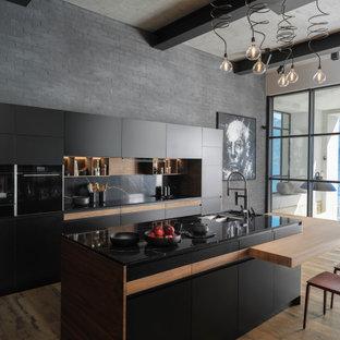 Идея дизайна: параллельная кухня среднего размера в современном стиле с черной техникой, островом, врезной раковиной, плоскими фасадами, белыми фасадами, черным фартуком, паркетным полом среднего тона, коричневым полом и черной столешницей