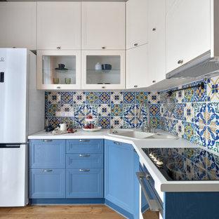 На фото: угловая кухня со шкафом над холодильником в стиле неоклассика (современная классика) с накладной раковиной, фасадами с утопленной филенкой, синими фасадами, белой техникой, паркетным полом среднего тона, коричневым полом, белой столешницей и разноцветным фартуком без острова с