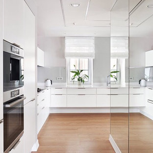 Inspiration for a large contemporary l-shaped open plan kitchen in Other with an undermount sink, flat-panel cabinets, white cabinets, solid surface benchtops, pink splashback, glass sheet splashback, stainless steel appliances, medium hardwood floors, brown floor and white benchtop.