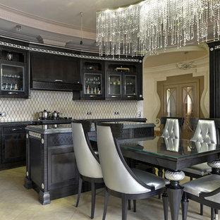 Стильный дизайн: кухня в стиле неоклассика (современная классика) с обеденным столом, фасадами с утопленной филенкой, черными фасадами, бежевым фартуком, островом, бежевым полом и черной столешницей - последний тренд