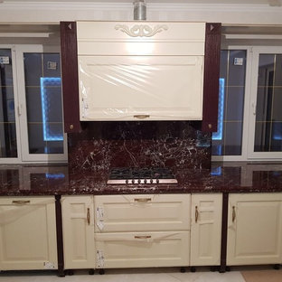 Photo of a large single-wall open plan kitchen in Other with beige cabinets, marble benchtops, red splashback, marble splashback, ceramic floors, no island, beige floor and red benchtop.