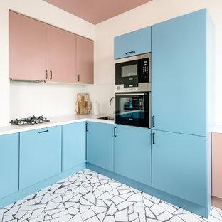 Создайте стильный интерьер: угловая кухня-гостиная в современном стиле с врезной раковиной, плоскими фасадами, синими фасадами, белым фартуком, техникой из нержавеющей стали, разноцветным полом и белой столешницей без острова - последний тренд