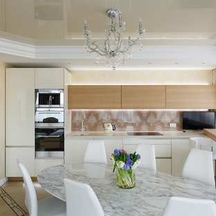 This is an example of a mid-sized eclectic single-wall open plan kitchen in Saint Petersburg with an undermount sink, medium wood cabinets, solid surface benchtops, multi-coloured splashback, glass sheet splashback, stainless steel appliances, ceramic floors, multi-coloured floor and beige benchtop.