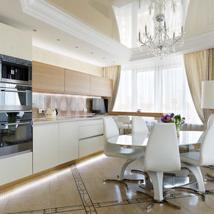Photo of a mid-sized contemporary single-wall open plan kitchen in Saint Petersburg with flat-panel cabinets, white cabinets, beige splashback, black appliances, a peninsula, an undermount sink, solid surface benchtops, glass sheet splashback, ceramic floors, multi-coloured floor and beige benchtop.