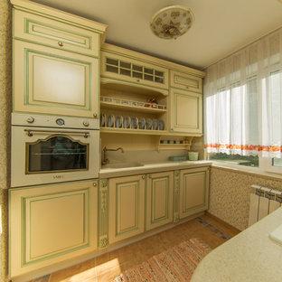 モスクワの小さいトラディショナルスタイルのおしゃれなキッチン (一体型シンク、レイズドパネル扉のキャビネット、ベージュのキャビネット、人工大理石カウンター、ベージュキッチンパネル、白い調理設備、セラミックタイルの床、アイランドなし) の写真