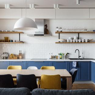 На фото: угловая кухня-гостиная в современном стиле с синими фасадами, белым фартуком, накладной раковиной, фасадами с утопленной филенкой, фартуком из плитки кабанчик, техникой из нержавеющей стали, коричневым полом, белой столешницей и паркетным полом среднего тона с