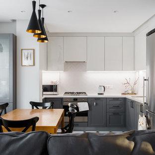 Создайте стильный интерьер: угловая кухня-гостиная в современном стиле с врезной раковиной, фасадами с утопленной филенкой, серыми фасадами, белым фартуком, техникой из нержавеющей стали и белой столешницей без острова - последний тренд