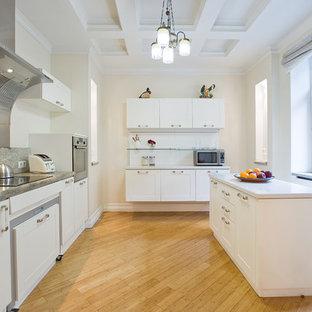 サンクトペテルブルクの広いコンテンポラリースタイルのおしゃれなキッチン (ドロップインシンク、フラットパネル扉のキャビネット、白いキャビネット、グレーのキッチンパネル、大理石のキッチンパネル、黒い調理設備、無垢フローリング、黄色い床) の写真