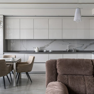 Design ideas for a mid-sized contemporary u-shaped eat-in kitchen in Saint Petersburg with an undermount sink, flat-panel cabinets, beige cabinets, marble benchtops, beige splashback, stone tile splashback, white appliances, marble floors, beige floor and grey benchtop.