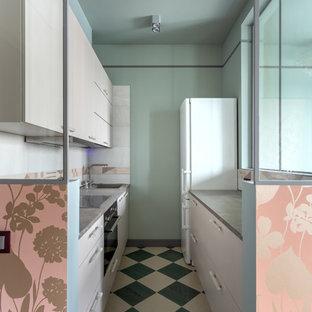 Выдающиеся фото от архитекторов и дизайнеров интерьера: маленькая параллельная, отдельная кухня в современном стиле с плоскими фасадами, столешницей из ламината, белым фартуком, фартуком из керамической плитки, черной техникой, полом из керамической плитки, разноцветным полом, накладной раковиной, белыми фасадами и серой столешницей без острова