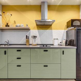 Источник вдохновения для домашнего уюта: прямая кухня-гостиная в современном стиле с накладной раковиной, плоскими фасадами, зелеными фасадами, белым фартуком, полом из ламината и серой столешницей без острова