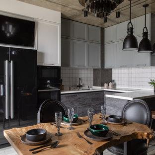 На фото: п-образные кухни - столовые в стиле лофт с врезной раковиной, фасадами с утопленной филенкой, серыми фасадами, белым фартуком, черной техникой, полуостровом и белой столешницей
