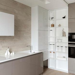 Пример оригинального дизайна: угловая кухня-гостиная в современном стиле с монолитной раковиной, плоскими фасадами, бежевым фартуком, черной техникой, светлым паркетным полом и бежевым полом без острова