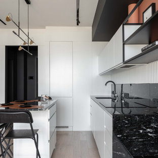 This is an example of a small scandinavian single-wall eat-in kitchen in Moscow with an undermount sink, flat-panel cabinets, white cabinets, granite benchtops, black splashback, granite splashback, black appliances, light hardwood floors, with island, grey floor and black benchtop.