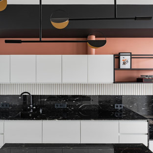 Photo of a small scandinavian single-wall eat-in kitchen in Moscow with an undermount sink, flat-panel cabinets, white cabinets, granite benchtops, black splashback, granite splashback, black appliances, medium hardwood floors, with island, grey floor and black benchtop.