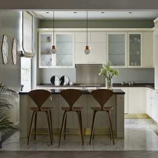 This is an example of a transitional l-shaped open plan kitchen in Other with a drop-in sink, flat-panel cabinets, quartzite benchtops, grey splashback, metal splashback, white appliances, porcelain floors, with island, white floor, brown benchtop and beige cabinets.