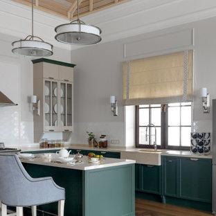 На фото: угловая кухня-гостиная в стиле современная классика с раковиной в стиле кантри, фасадами с утопленной филенкой, зелеными фасадами, белым фартуком, темным паркетным полом, островом, коричневым полом, белой столешницей и потолком из вагонки