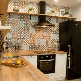 Inredning av ett nordiskt mellanstort brun brunt kök, med en undermonterad diskho, luckor med upphöjd panel, vita skåp, träbänkskiva, flerfärgad stänkskydd, stänkskydd i porslinskakel, integrerade vitvaror, klinkergolv i porslin och brunt golv