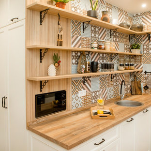 Photo of a small scandinavian l-shaped separate kitchen in Other with a single-bowl sink, recessed-panel cabinets, white cabinets, wood benchtops, multi-coloured splashback, ceramic splashback, black appliances, no island and beige benchtop.