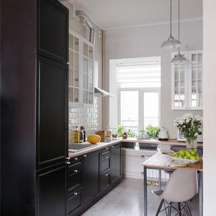 Новый формат декора квартиры: маленькая линейная кухня в классическом стиле с обеденным столом, врезной раковиной, черными фасадами, белым фартуком, фартуком из керамической плитки, черной техникой и паркетным полом среднего тона без острова