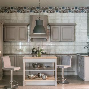 Стильный дизайн: угловая кухня в современном стиле с накладной раковиной, фасадами с выступающей филенкой, серыми фасадами, серым фартуком, фартуком из зеркальной плитки, техникой из нержавеющей стали, островом, бежевым полом и коричневой столешницей - последний тренд