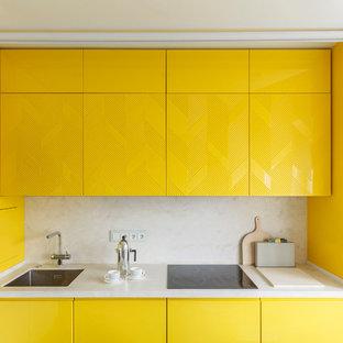 Пример оригинального дизайна: отдельная, угловая кухня в современном стиле с врезной раковиной, плоскими фасадами, желтыми фасадами, белым фартуком и черной техникой без острова