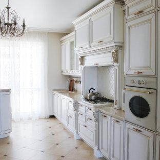 На фото: большая отдельная, прямая кухня в викторианском стиле с монолитной раковиной, фасадами с выступающей филенкой, белыми фасадами, столешницей из акрилового камня, белым фартуком, фартуком из керамической плитки, белой техникой, полом из керамогранита, бежевым полом и бежевой столешницей