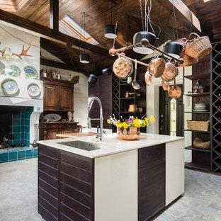 На фото: большая кухня в стиле кантри с обеденным столом, врезной раковиной, плоскими фасадами, коричневыми фасадами, мраморной столешницей, полом из сланца, островом, серым полом и бежевой столешницей с