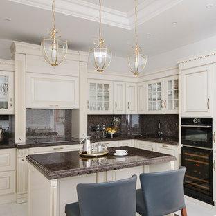 Пример оригинального дизайна: угловая кухня-гостиная в классическом стиле с одинарной раковиной, стеклянными фасадами, бежевыми фасадами, коричневым фартуком, черной техникой, островом и коричневой столешницей