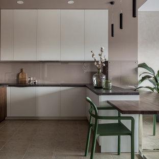 На фото: маленькая п-образная кухня-гостиная в современном стиле с плоскими фасадами, белыми фасадами, столешницей из ламината, черной техникой, полом из керамогранита, полуостровом, черной столешницей, врезной раковиной, серым фартуком, фартуком из стекла и серым полом с